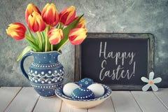 tulipanes Rojo-amarillos en jarra de cerámica azul con los huevos de Pascua y a Fotografía de archivo