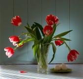 Tulipanes rojos en el florero cristalino con los huevos Fotos de archivo