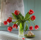 Tulipanes rojos en el florero cristalino con los huevos Fotografía de archivo libre de regalías