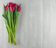 Tulipanes rojos en Gray Table Top resistido fotografía de archivo