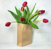 Tulipanes rojos en saco marrón fotos de archivo