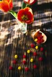 Tulipanes rojos florecientes en un fondo de madera con los dulces Foto de archivo libre de regalías