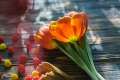 Tulipanes rojos florecientes en un fondo de madera con los dulces Fotos de archivo
