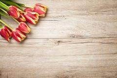 Tulipanes rojos que mienten en la tabla rústica vieja de madera Imagen de archivo libre de regalías