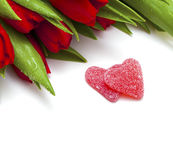 Tulipanes rojos y dos caramelos en forma de corazón Imagen de archivo libre de regalías