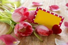 Tulipanes rosados con la tarjeta en el fondo de madera Foto de archivo