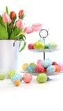 Tulipanes rosados con los huevos de Pascua coloridos en blanco Foto de archivo