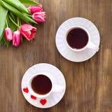 Tulipanes rosados en fondo de madera, dos tazas de té y café en los platillos con la mermelada de los corazones Fotografía de archivo libre de regalías