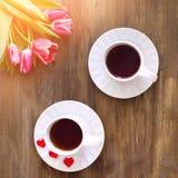 Tulipanes rosados en fondo de madera, dos tazas de té y café en los platillos con la mermelada de los corazones Fotos de archivo libres de regalías
