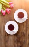 Tulipanes rosados en fondo de madera, dos tazas de té y café en los platillos con la mermelada de los corazones Imagen de archivo libre de regalías