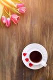 Tulipanes rosados en fondo de madera, dos tazas de té y café en los platillos con la mermelada de los corazones Foto de archivo libre de regalías