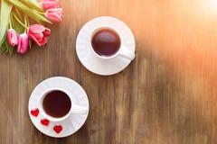 Tulipanes rosados en fondo de madera, dos tazas de té y café en los platillos con la mermelada de los corazones Imagen de archivo