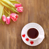 Tulipanes rosados en fondo de madera, dos tazas de té y café en los platillos con la mermelada de los corazones Foto de archivo