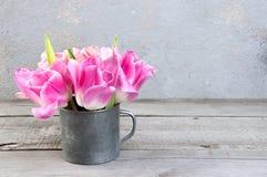 Tulipanes rosados en taza del metal del vintage Fotos de archivo libres de regalías