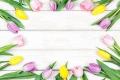 Tulipanes rosados y amarillos en un fondo de madera blanco Imagen de archivo libre de regalías