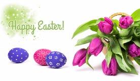 Tulipanes rosados y huevos de Pascua pintados en el fondo blanco Imagen de archivo