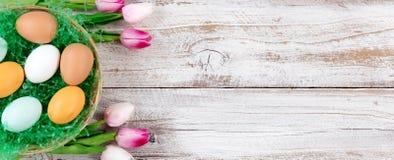 Tulipanes rosados y huevos reales para Pascua en la parte posterior de madera blanca rústica Fotografía de archivo