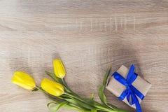Tulipanes y caja de regalo amarillos con la cinta azul en un backgrou de madera Fotos de archivo libres de regalías