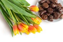 Tulipanes y caramelos de chocolate Fotografía de archivo