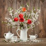 Tulipanes y flor de cerezo en una tabla adornada Fotografía de archivo