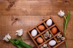 Tulipanes y huevos blancos en caja de madera en la tabla Visión superior imagen de archivo libre de regalías
