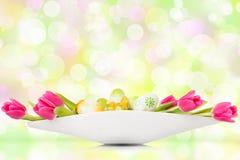 Tulipanes y huevos de Pascua antes del fondo del bokeh Imagenes de archivo