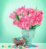 Tulipanes y huevos de Pascua rosados del chocolate Todavía de las flores vida Imagenes de archivo
