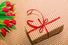 Tulipanes y paquete del regalo con un arco rojo Foto de archivo