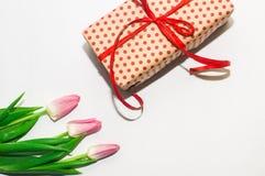 Tulipanes y paquete del regalo con un arco rojo Fotografía de archivo libre de regalías