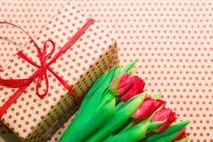 Tulipanes y paquete del regalo con un arco rojo Fotografía de archivo