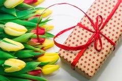 Tulipanes y paquete del regalo en un fondo blanco Imágenes de archivo libres de regalías