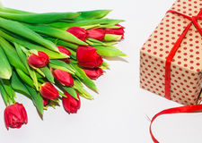 Tulipanes y paquete del regalo en un fondo blanco Foto de archivo libre de regalías