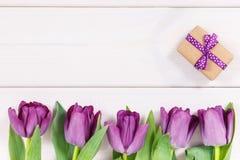 Tulipanes y regalo púrpuras para diversas ocasiones, espacio de la copia para el texto en los tableros blancos Fotografía de archivo