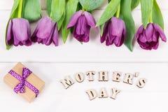 Tulipanes y regalo púrpuras para el día del ` s de la madre en los tableros blancos Fotos de archivo libres de regalías