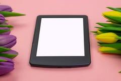 Tulipanes y tableta con la pantalla blanca de la maqueta en fondo rosado Tarjeta de felicitaci?n para Pascua o el d?a de las muje imagen de archivo libre de regalías