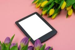 Tulipanes y tableta con la pantalla blanca de la maqueta en fondo rosado Tarjeta de felicitaci?n para Pascua o el d?a de las muje fotos de archivo libres de regalías