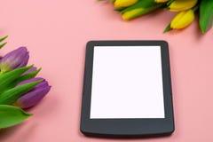Tulipanes y tableta con la pantalla blanca de la maqueta en fondo rosado Tarjeta de felicitaci?n para Pascua o el d?a de las muje imagenes de archivo