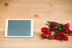 Tulipanes y tableta rojos hermosos en un fondo de madera fotos de archivo