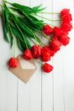 Tulipanes y tarjeta de felicitación frescos sobre fondo de madera de la tabla Fotos de archivo libres de regalías