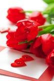 Tulipanes y tarjeta de felicitación rojos Fotos de archivo libres de regalías