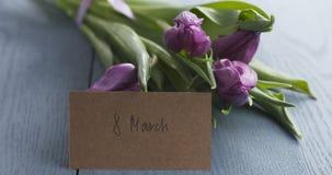 Tulipani con la cartolina d'auguri dell'8 marzo sulla tavola blu Fotografie Stock