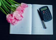 Tulipani con la penna ed il calcolatore sul taccuino vuoto immagine stock libera da diritti