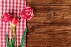 Tulipani con la tovaglia a quadretti rossa sul fondo di legno del paese Vista superiore, spazio del testo fotografia stock