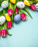 Tulipani con le uova di Pasqua variopinte Fotografie Stock