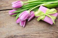 Tulipani con un contenitore di regalo su vecchio di legno Fotografia Stock