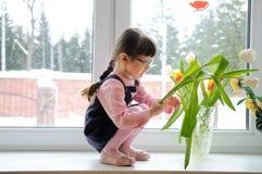 Tulipani del wiyh della bambina in inverno Fotografia Stock Libera da Diritti