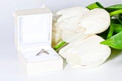 Tulipani bianchi della molla con la scatola con l'anello di diamante Fotografie Stock