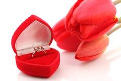 Tulipani e contenitore di monili rossi con l'anello Immagini Stock