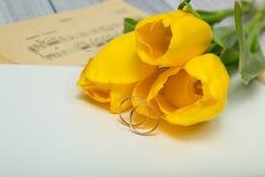 Tulipani e fedi nuziali gialli Fotografia Stock