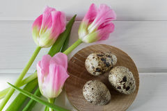 Tulipani ed uova di Pasqua rosa freschi su fondo bianco immagini stock